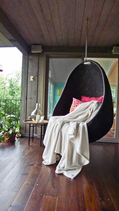 a stylish black egg-shaped hanging chair is a bold idea for a modern porch