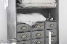 25 an apothecary cabinet painted light grey and renovated into a linen storage item