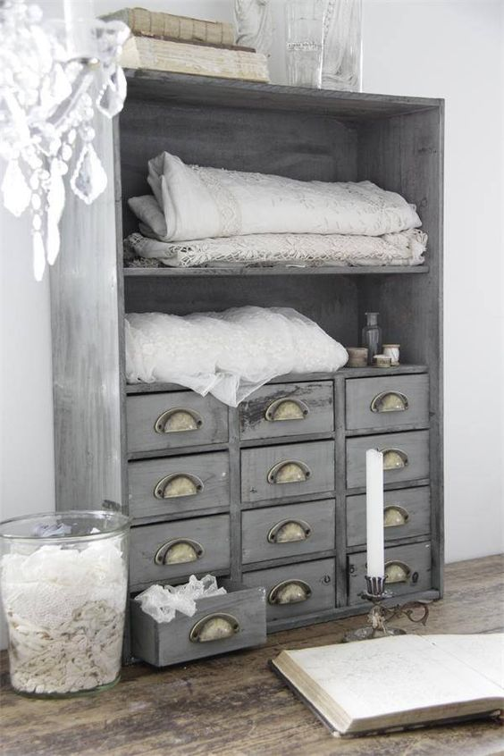 an apothecary cabinet painted light grey and renovated into a linen storage item