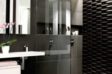 25 large scale black tiles and a textural black tile wall in the shower for a modern look