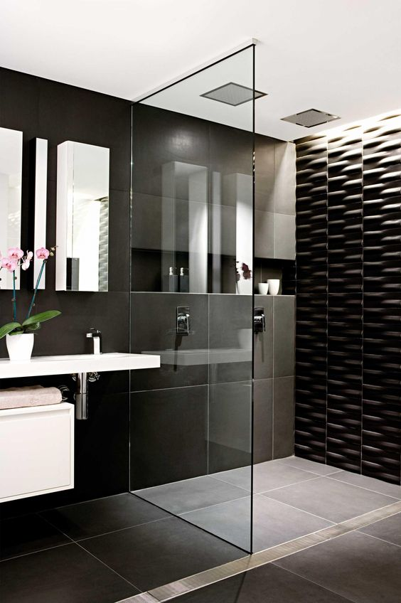 large scale black tiles and a textural black tile wall in the shower for a modern look