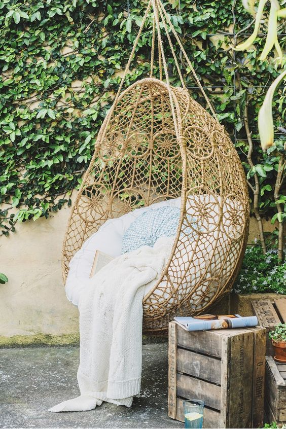 a boho inspired hanging chair with pillows and a blanket in the patio