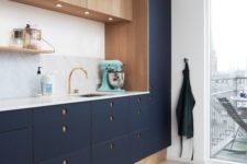 26 a modern cool kitchen in navy and wood with round holes as handles, a marble counterop and backsplash
