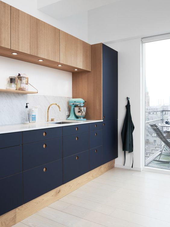 a modern cool kitchen in navy and wood with round holes as handles, a marble counterop and backsplash