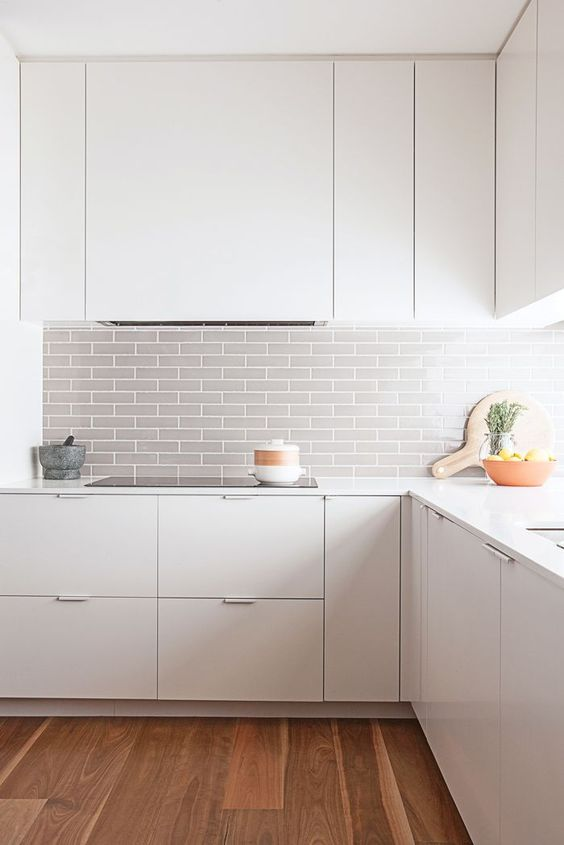 a modern white space is made more eye-catchy with a grey tile backsplash and wooden floors