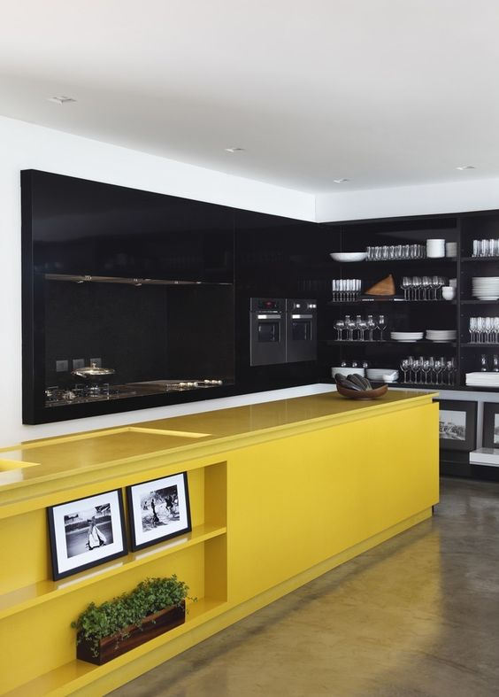a moody black kitchen with a bold yellow kitchen island with lots of storage