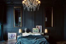 26 a moody luxurious bedroom with black panel walls, vintage mirrors and a chandelier and stunning parquet floors
