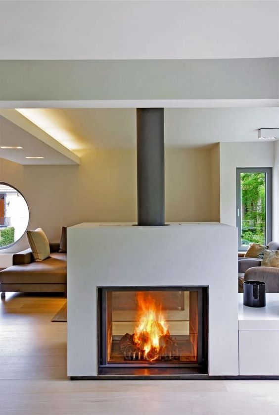 a wood burning closed stove visible from both sides is a gorgeous modern idea to bring warmth
