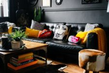 26 an eclectic space with black walls and furniture, a unique chandelier, framed artworks and clorful touches