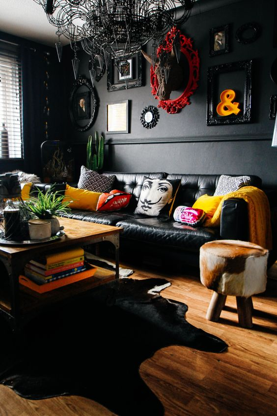 an eclectic space with black walls and furniture, a unique chandelier, framed artworks and clorful touches