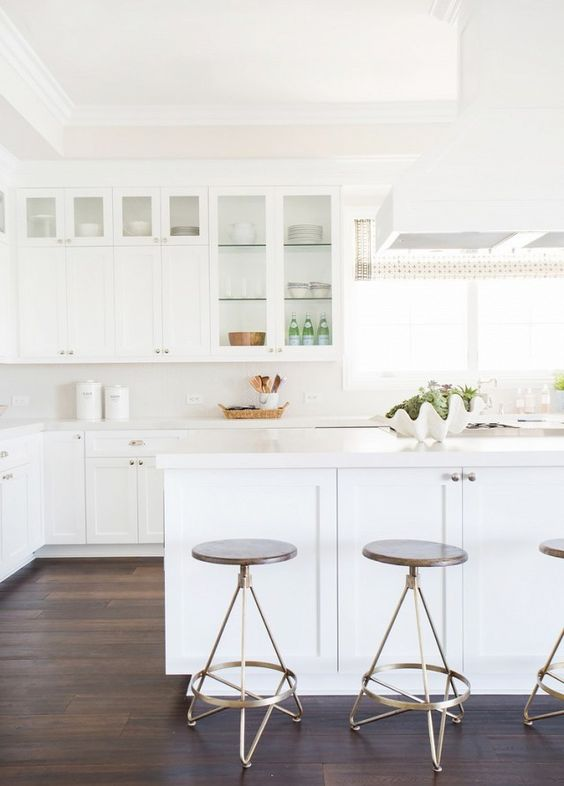 a simple white kitchen with glass cabinets and a large kitchen island leaves an airy feeling