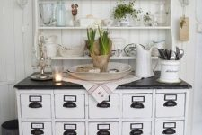 27 an apothecary cabinet with a black counter and handles as a vintage kitchen table and storage item