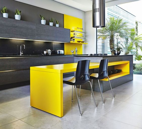 an ultra-modern kitchen with dark grey cabinets and a yellow kitchen island for a dining space