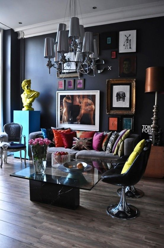 to balance a moody feel from the black walls, colorful textiles and artworks were used here, which made the space more contrasting
