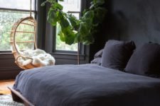 28 a welcoming space with black walls, a dark wooden bed and dark bedding is filled with light from several windows