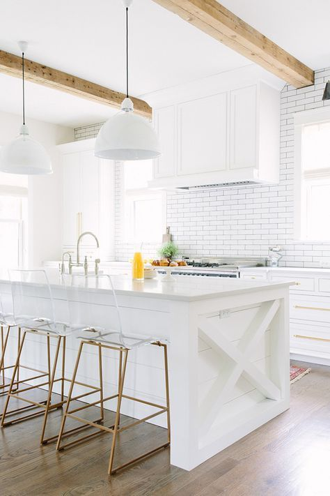 a white rustic kitchen with a subway tile backsplash and wooden beams to make it more eye-catching