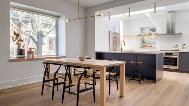 The dining room and kitchen are united, they are filled with natural light, with wishbone chairs and dark grey kitchen cabinets with white countertops