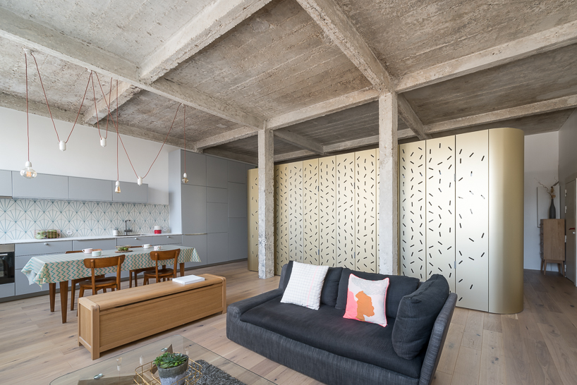 This Parisian loft features an interesting piece   a central island with perforated panels that divides spaces and contains a bedroom inside