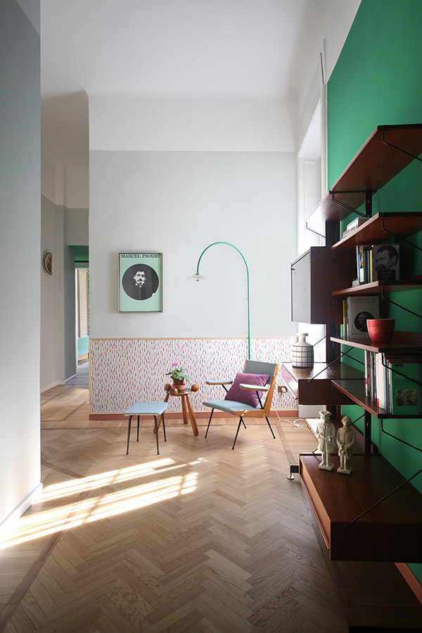 This colorful space is done with a green statement wall, colorful wallpaper and lots of floating shelves and drawers