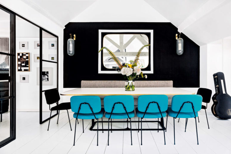 The dining space is done with a black accent wall, cool wall lamps and bold turquoise chairs