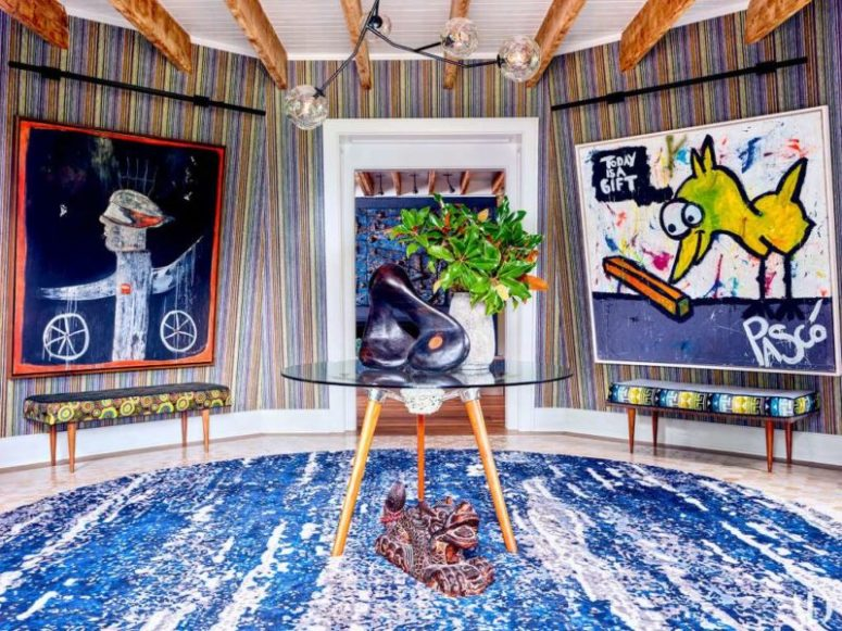 The entry is done in the bold shades of blue, with colorful upholstered benches and very bold artworks