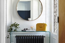 02 The entryway is done with a round mirror, a plexiglass console and greenery