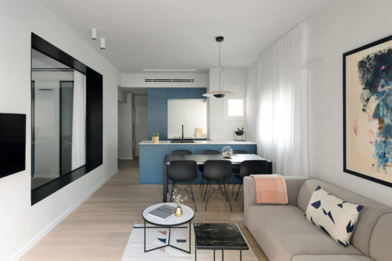 The kitchen and living room are united into one space, the cabinets are done in smoky blue, there's a small dining space with a black dining set and some grey upholstered furniture in the living zone