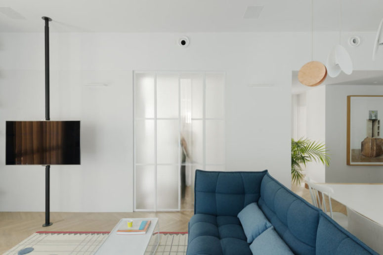 The living room features a blue sofa, a suspended TV, the doors are made of frosted glass, which doesn't make space dividing so harsh and still separates them