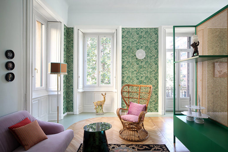 The living room is decorated with botanical print wallpaper, colorful upholstered furniture and a green dresser with a space divider