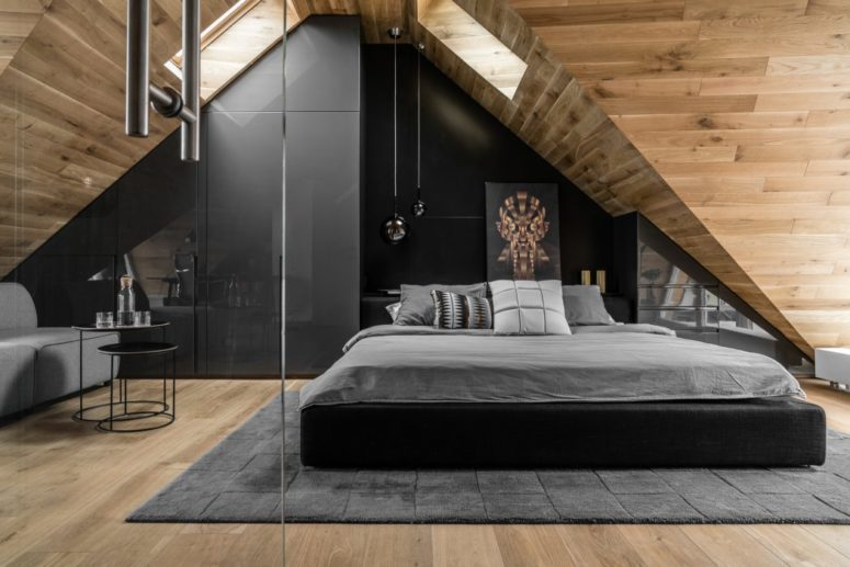 There's a black statement wall, an upholstered bed and an eye-catchy artwork, and skylights fill the space with light