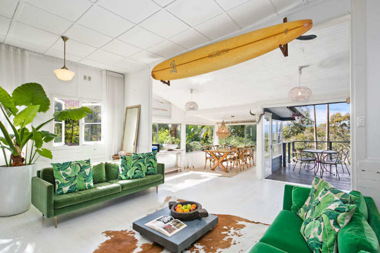 There's a surf over the entrance, and the room opens to a terrace and is connected to the dining space, there is potted greenery that refreshes the space