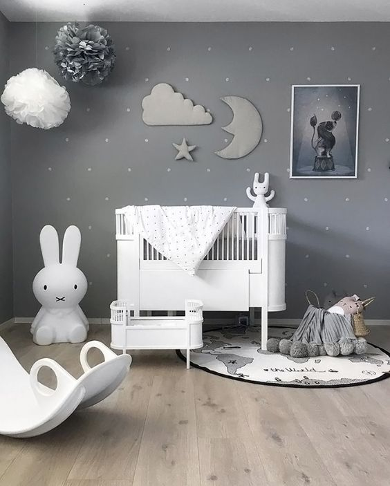 a beautiful grey nursery with a sky theme, paper pompoms and a stuffed cloud, moon and star