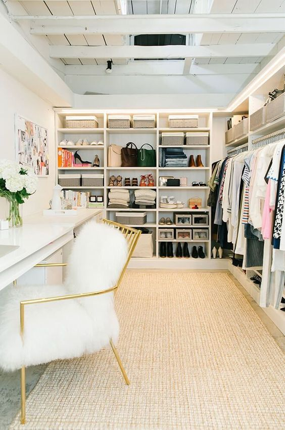 a girlish walk in closet in glam style, with a gilded chair, faux fur and open shelving, there's also a makeup vanity