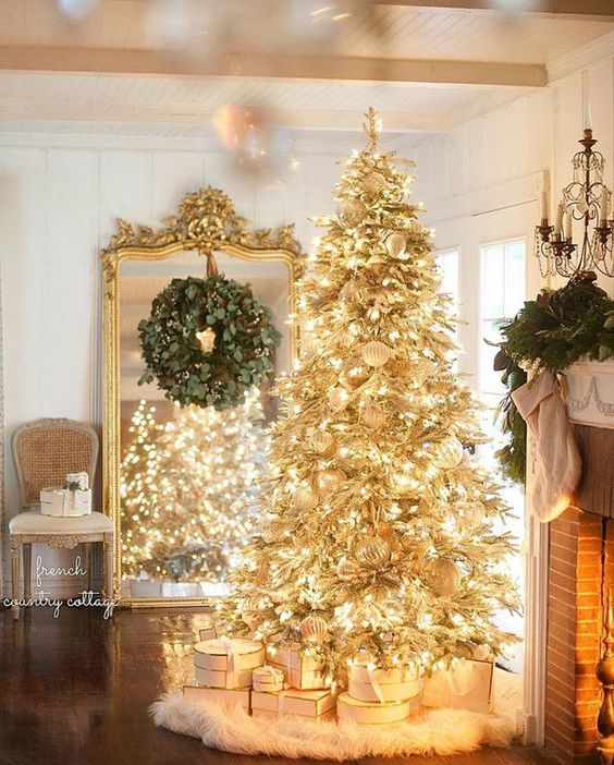 a gold pre-lit Christmas tree with white ornaments and a faux fur skirt