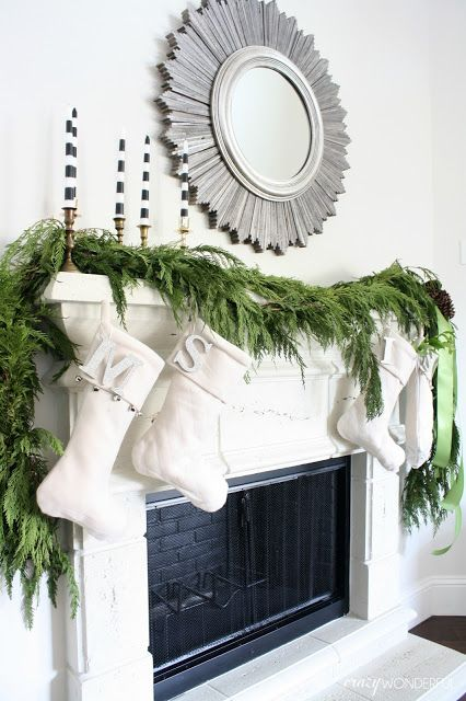 a lush evergreen garland, creamy stockings and striped candles make up a modern look with a rustic feel