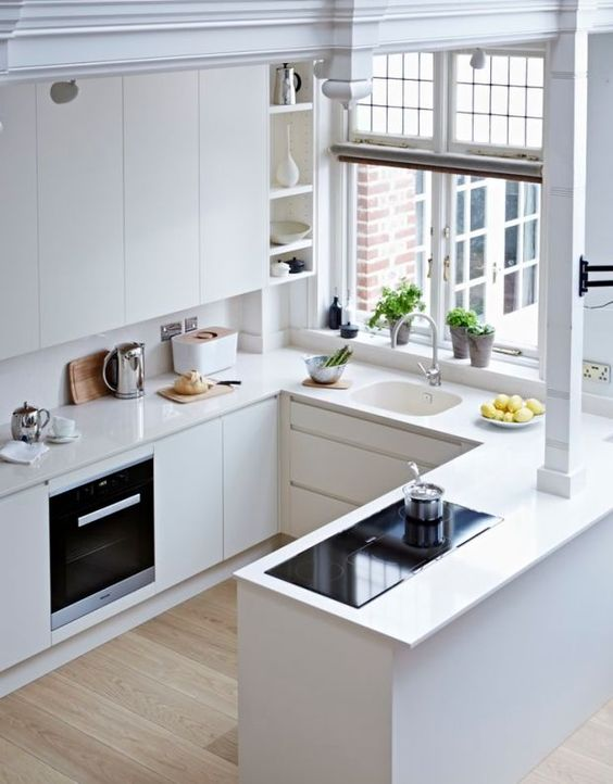 a minimalist white kitchen with sleek cabinets and a large window to fill the space with light