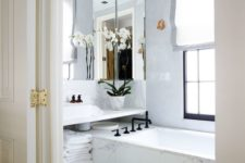 02 all-marble bathroom with a large mirror that takes almost the whole wall