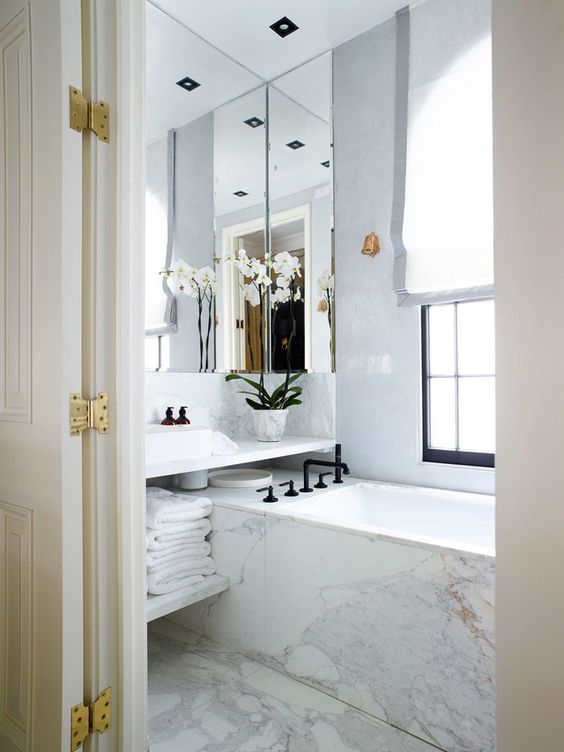 all-marble bathroom with a large mirror that takes almost the whole wall