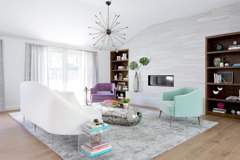 the first living room is done in white, there is colorful furniture, built-in bookcases and a mirror pebble table