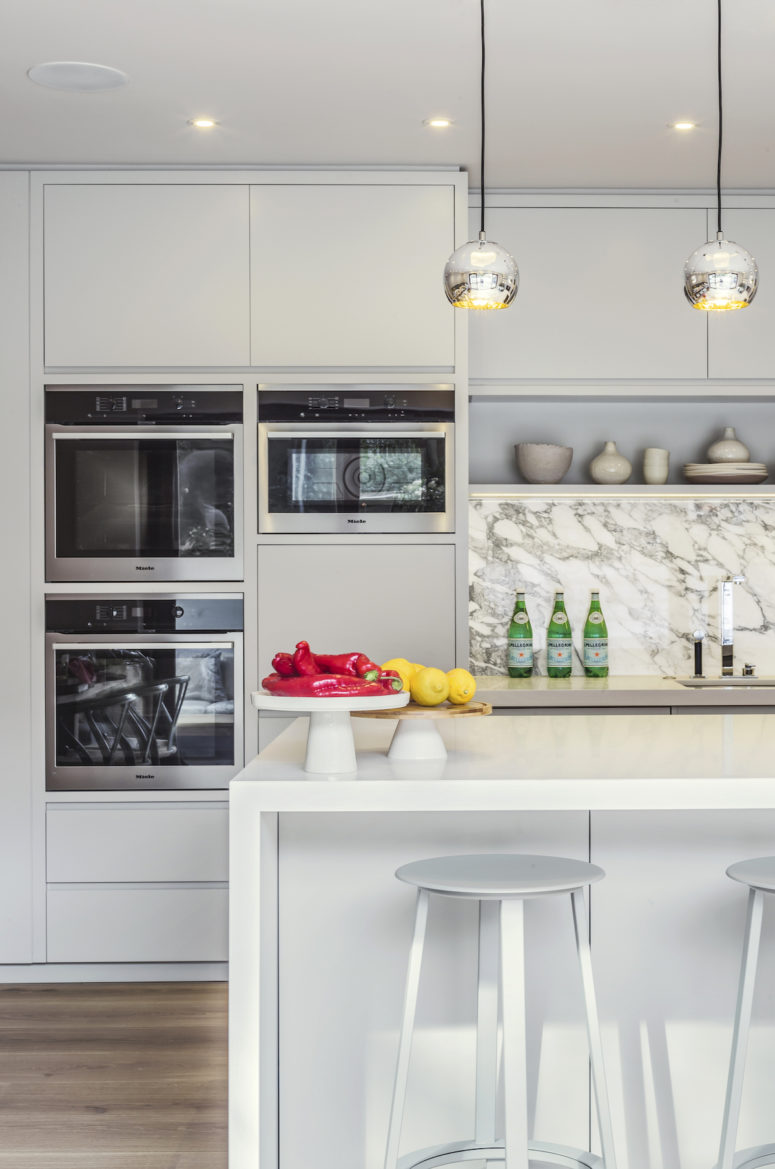 The appliances are built-in and the backsplash is marble
