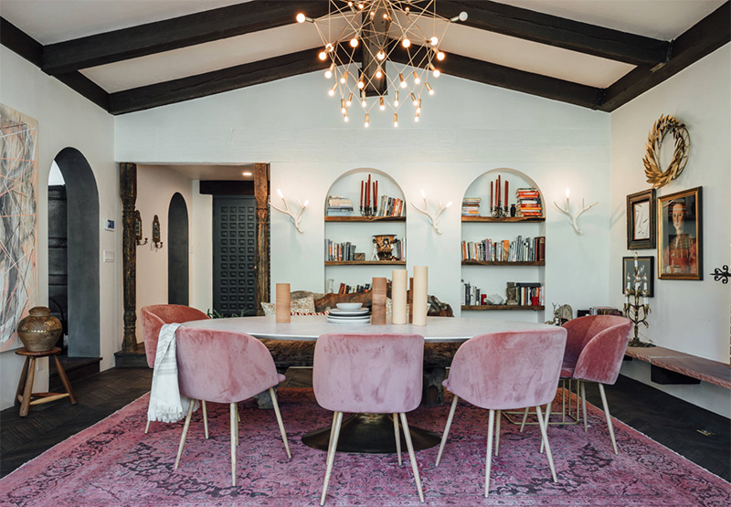 The dining space is done with black ceiling beams, dusty pink chairs and buil in bookshelves that remind of castles