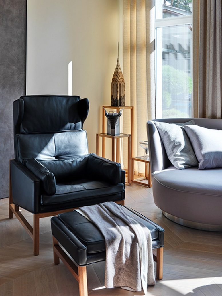 The furniture is comfy, there's a black leather chair with a footrest, a small upholstered sofa