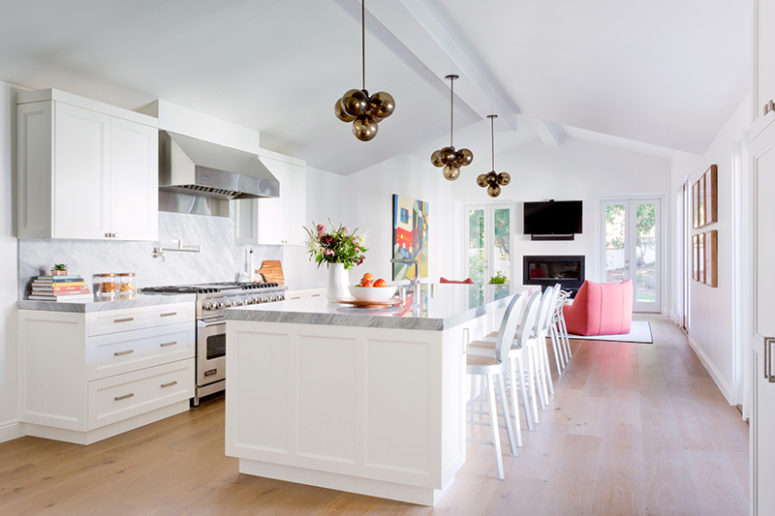 The kitchen is airy and light-colored, there's a sitting space with coral chairs and a built-in fireplace