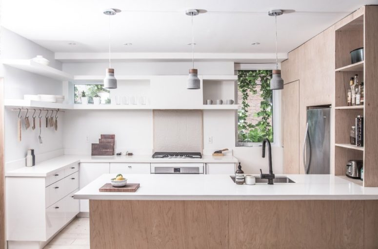 The kitchen is done in white and with light-colored wood, there are modern concrete pendant lamps and two small windows to bring light in