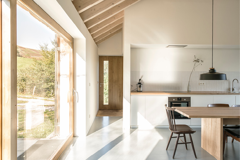 The kitchen is open, there are cabinets only downwards, and the space is filled with light through oversized windows
