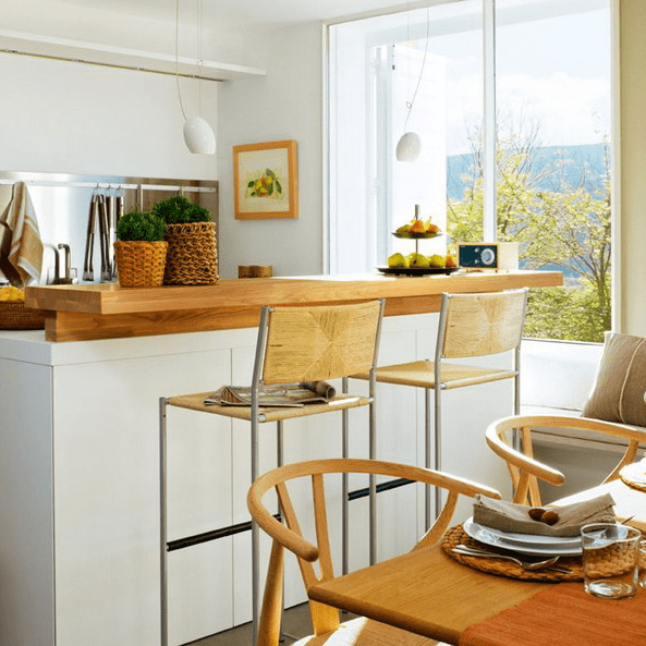 The kitchen island features a breakfast space or a mini bar countertop
