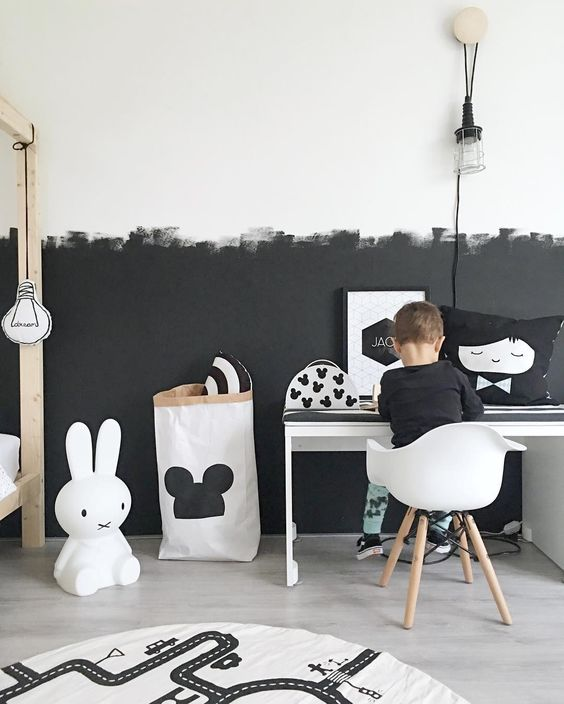 a Scandinavian kid's room with a partly black and partly white wall with a brushstroke pattern
