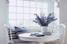03 a coastal breakfast nook with an upholstered windowsill bench, a round pedestal table and some chairs