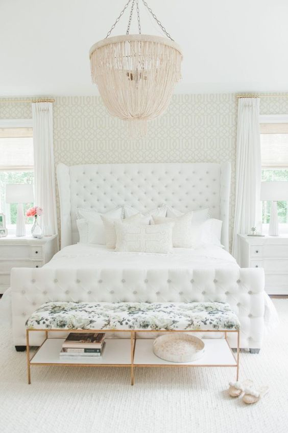 a creamy bedroom with a blush chandelier and a floral print upholstered bench