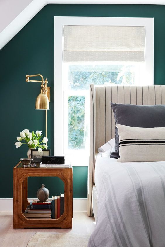 a gorgeous brass sconce with a vintage-inspired design looks amazing on an emerald wall